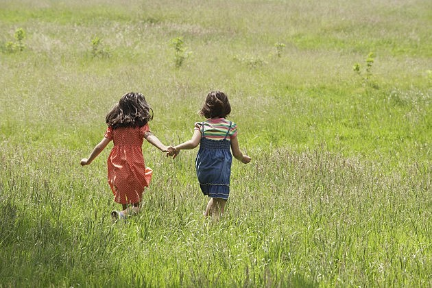 Girls Walking Together In Grassy Field